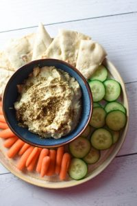 Artichoke hummus in a blue bowl surrounded by cucumber, carrots, and pita bread on a white surface