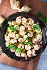 Shrimp in a cast iron pan with garlic and parsley on top. The pan is on a cutting board with sliced bread.