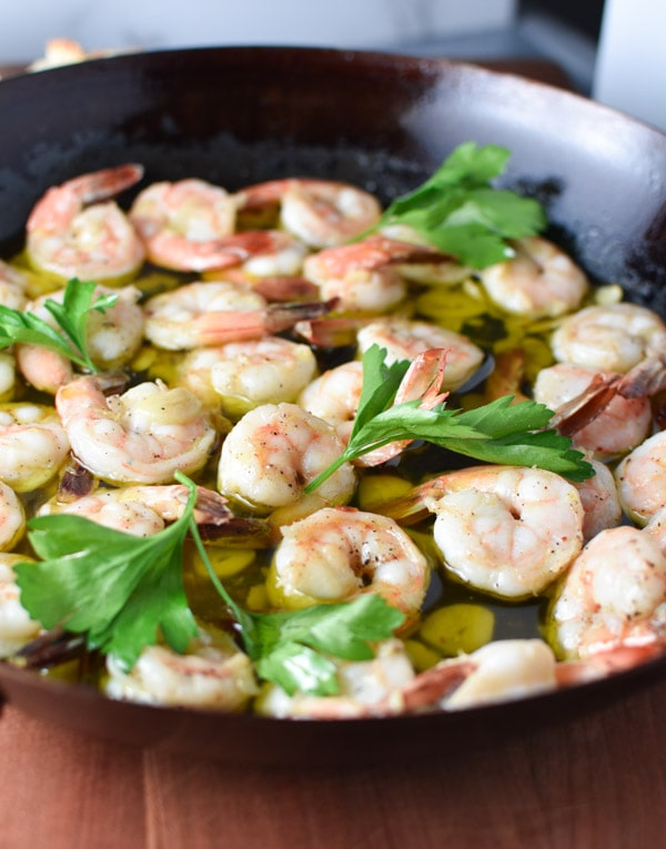 Shrimp being cooked in a pan with garlic and olive oil