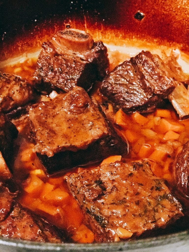Short ribs being braised with carrots in a dutch oven