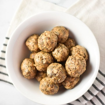 energy balls in a white bowl on a towel