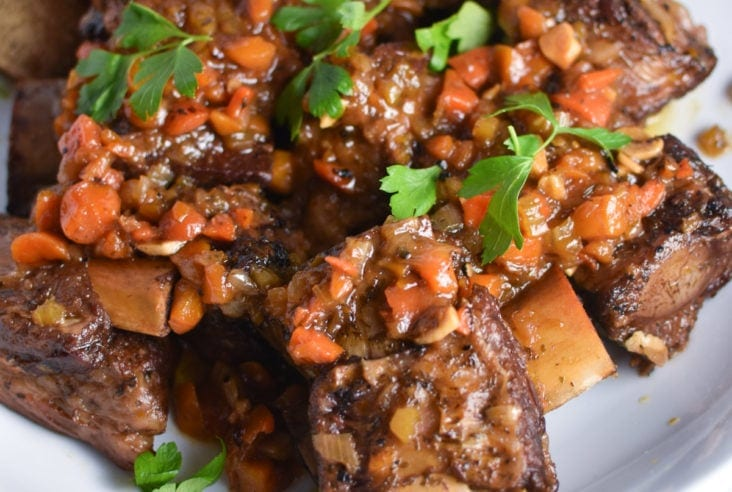 short ribs on a white plate sprinkled with carrots and parsley