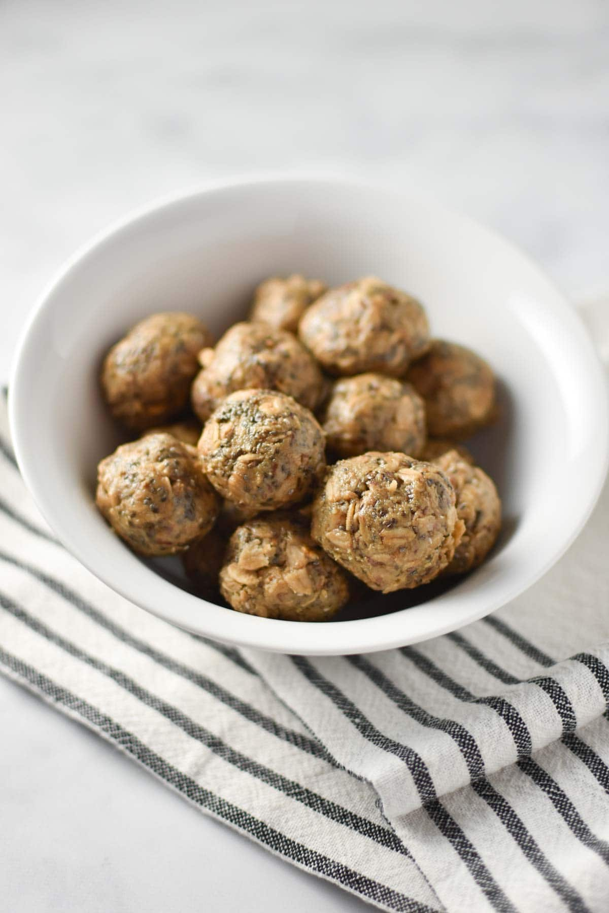 A bowl of sunbutter balls with oats and chia on a striped towel