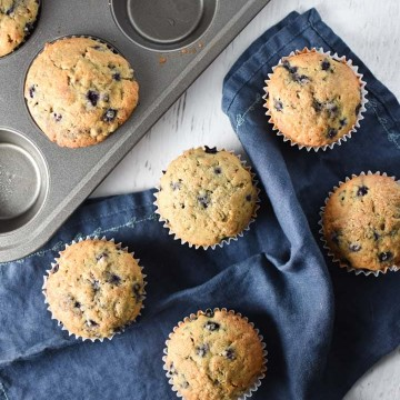 Blueberry muffins on a table next to a muffin pan and blue towel
