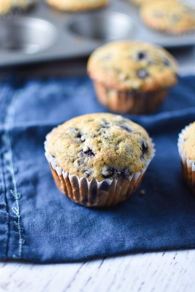 A single blueberry muffin on a blue napkin