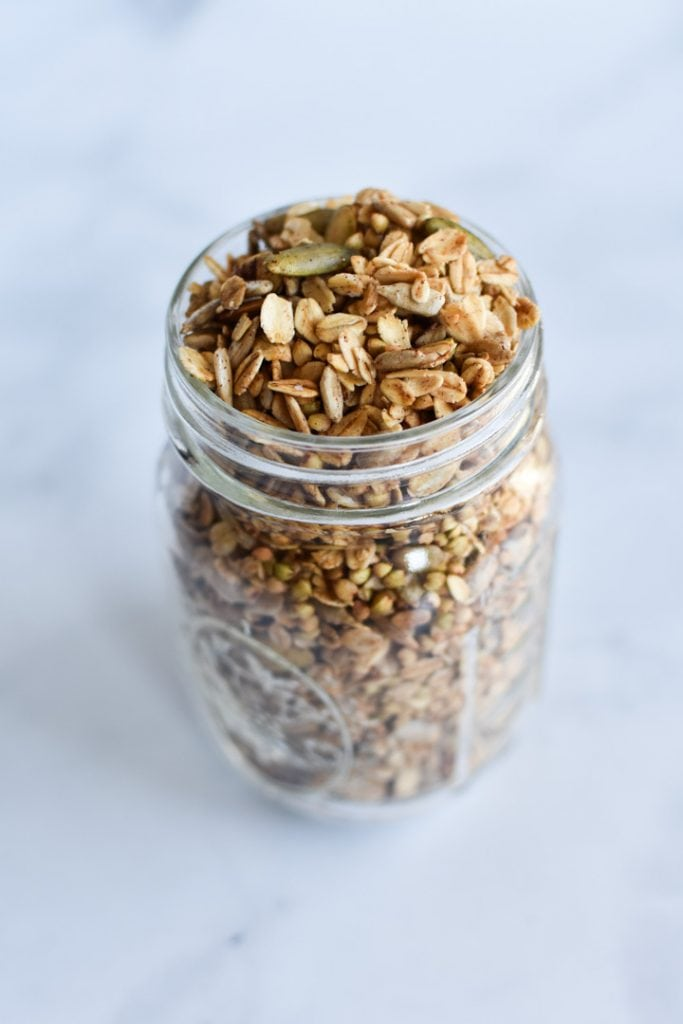 A mason jar with granola on a marble table
