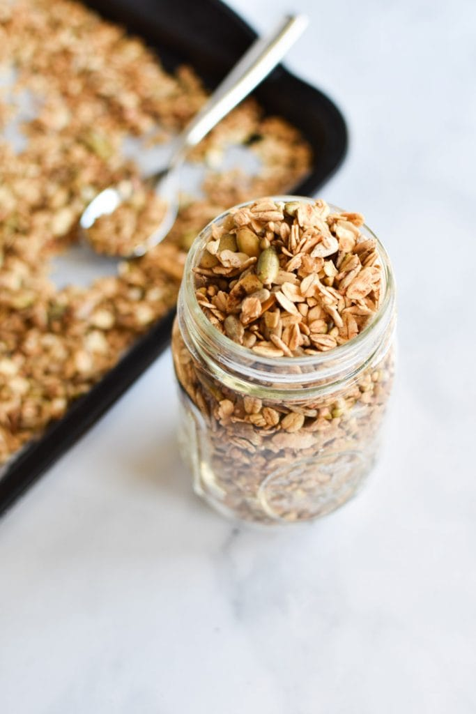 A mason jar of buckwheat granola next to a sheet pan with extra granola