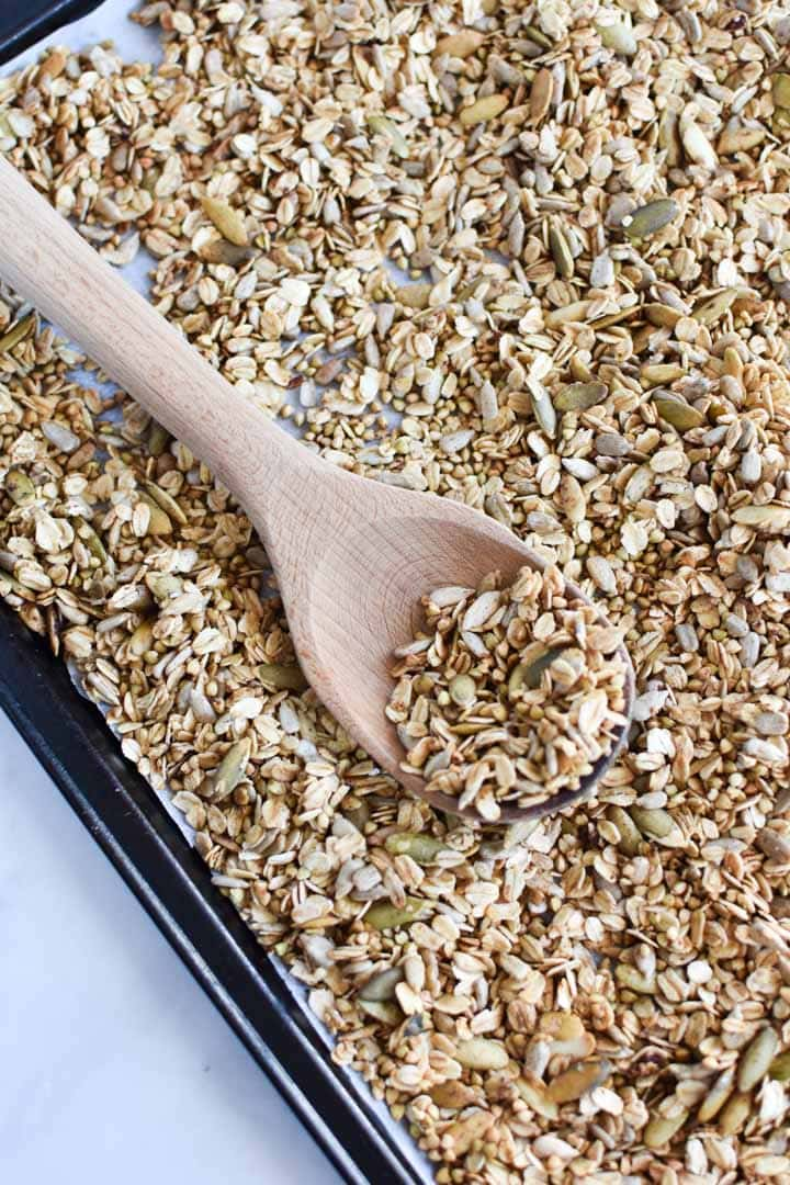 A wooden spoon scooping buckwheat granola from a sheet pan