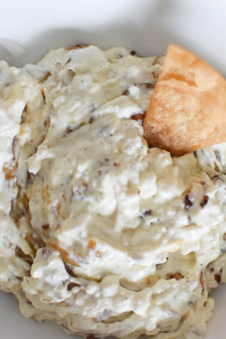 Caramelized shallot dip without sour cream in a white bowl with a chip
