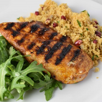 Grilled chicken next to couscous with pomegranate seeds and green arugula on a white plate