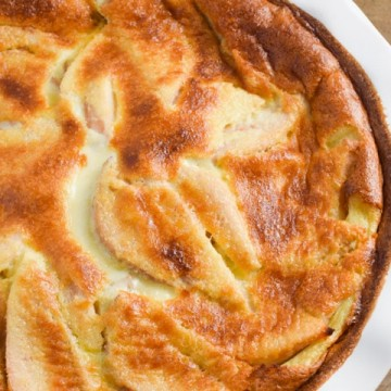 Pear Clafouti in a white baking dish on a wooden table