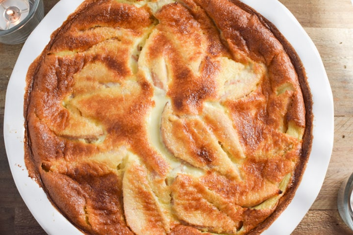 A white dish with pear clafoutis surrounded by candles