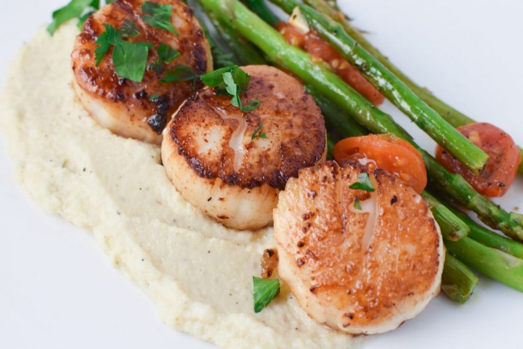 Scallops with chive oil, pureed cauliflower, and roasted asparagus. A great date night dinner or holiday meal #datenight #scallops #chives #asparagus #holidaymeal