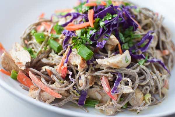 Soba noodles coated in a sunflower seed butter sauce topped with cilantro and carrots on a white plate
