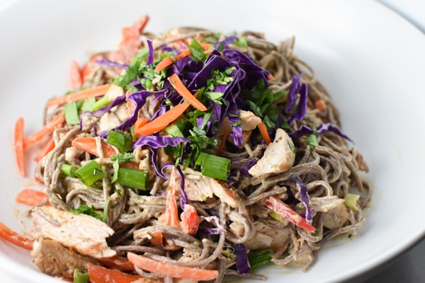 Soba noodles with carrots, cabbage, and green onion in a white bowl