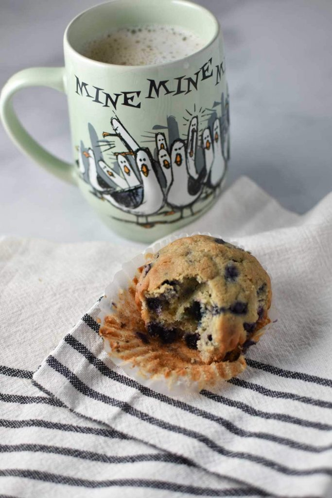 Blueberry muffin on a towel with a cup of coffee