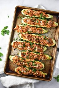 Zucchini boats stuffed with tomatoes, cheese and sweet Italian chicken sausage. This recipe cooks in under 30 minutes and is perfect for a family weeknight meal that's low carb, keto, and migraine diet friendly. #zucchiniboats #lowcarb #migrainediet #keto