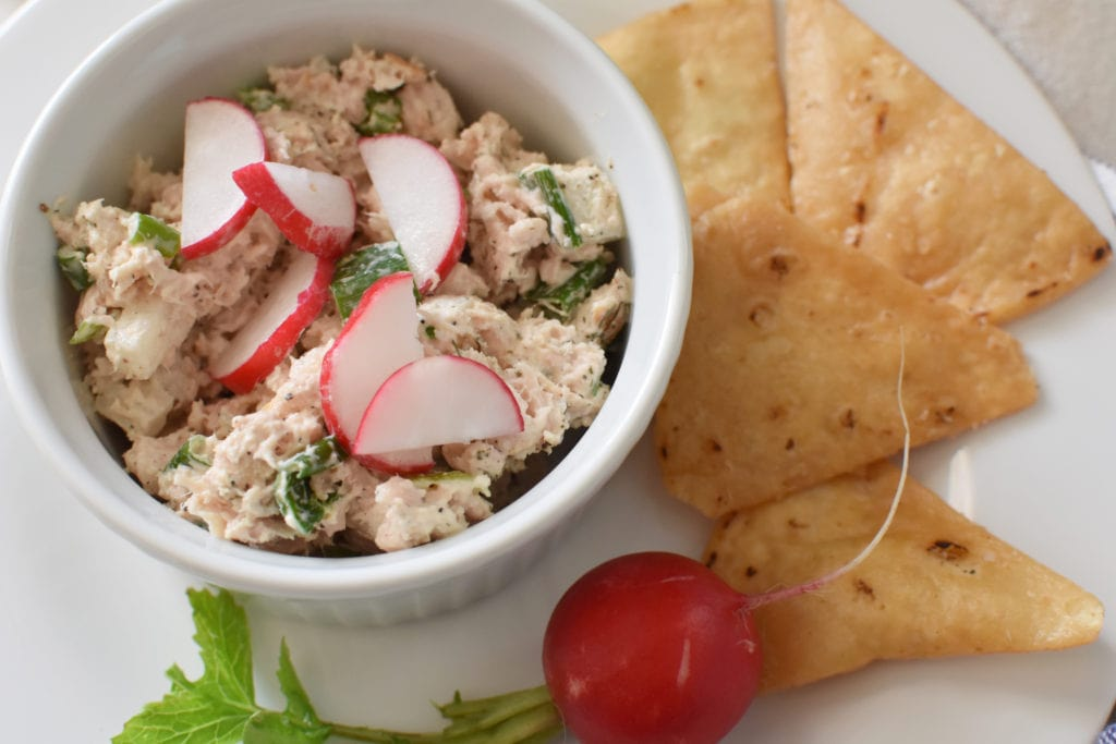 Tuna salad in a white bowl with pita chips and radishes