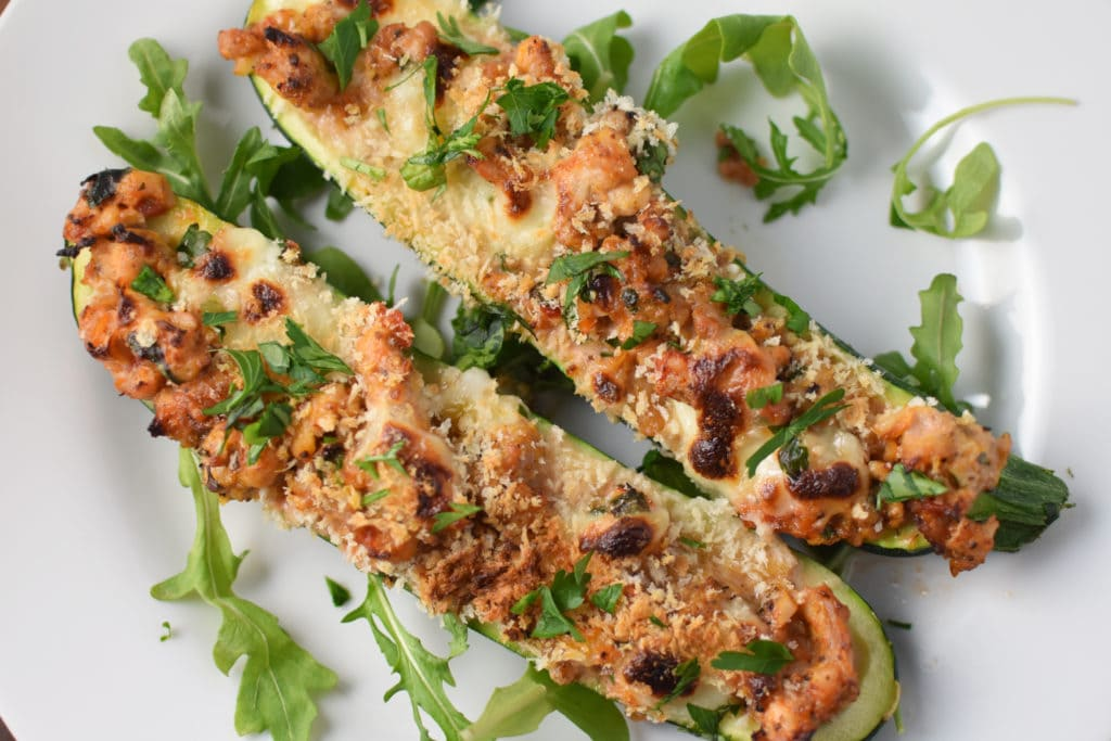 Two stuffed chicken zucchini boats with melted cheese and panko on top