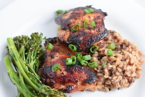Honey garlic chicken thighs with rice and broccolini, topped with green onions, on a white plate