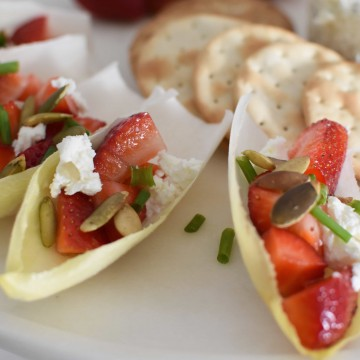 Endive filled with strawberries, goat cheese, pepitas and chives