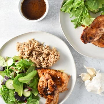 Two plates of garlic chicken with sauce, a simple salad, and rice