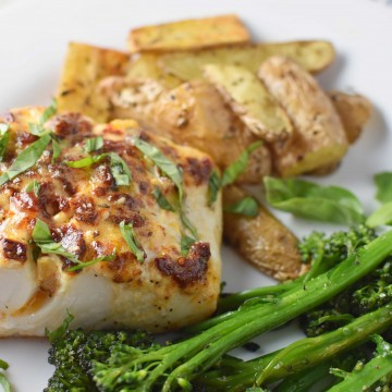Mediterranean baked halibut on a white plate with broccoli and potatoes with a dish towel in the back