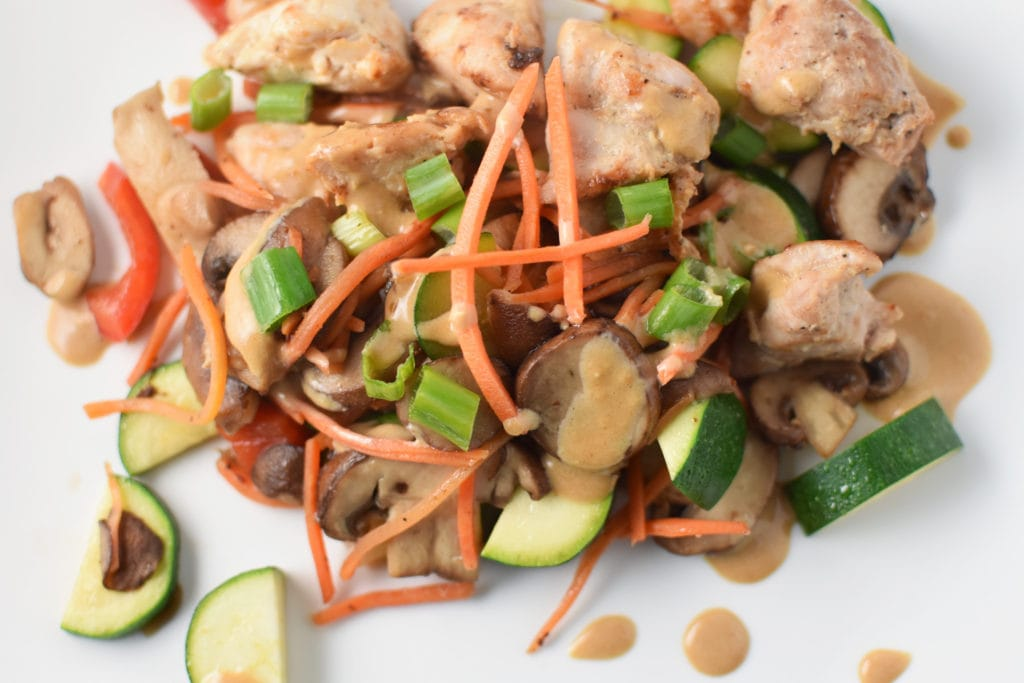 A spicy chicken stir fry with sesame sauce and veggies on a white plate