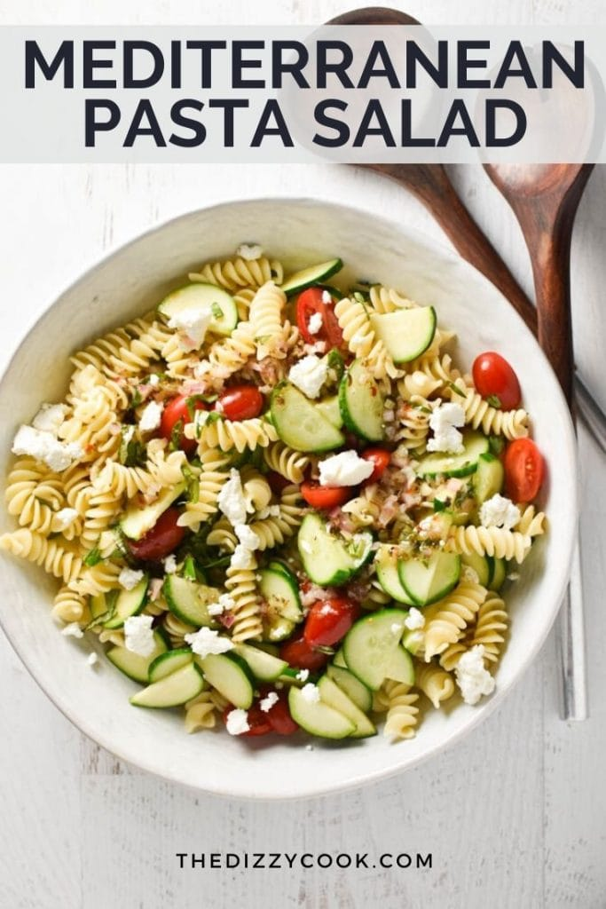 A white bowl of gluten free pasta salad with tomatoes and zucchini next to salad tongs
