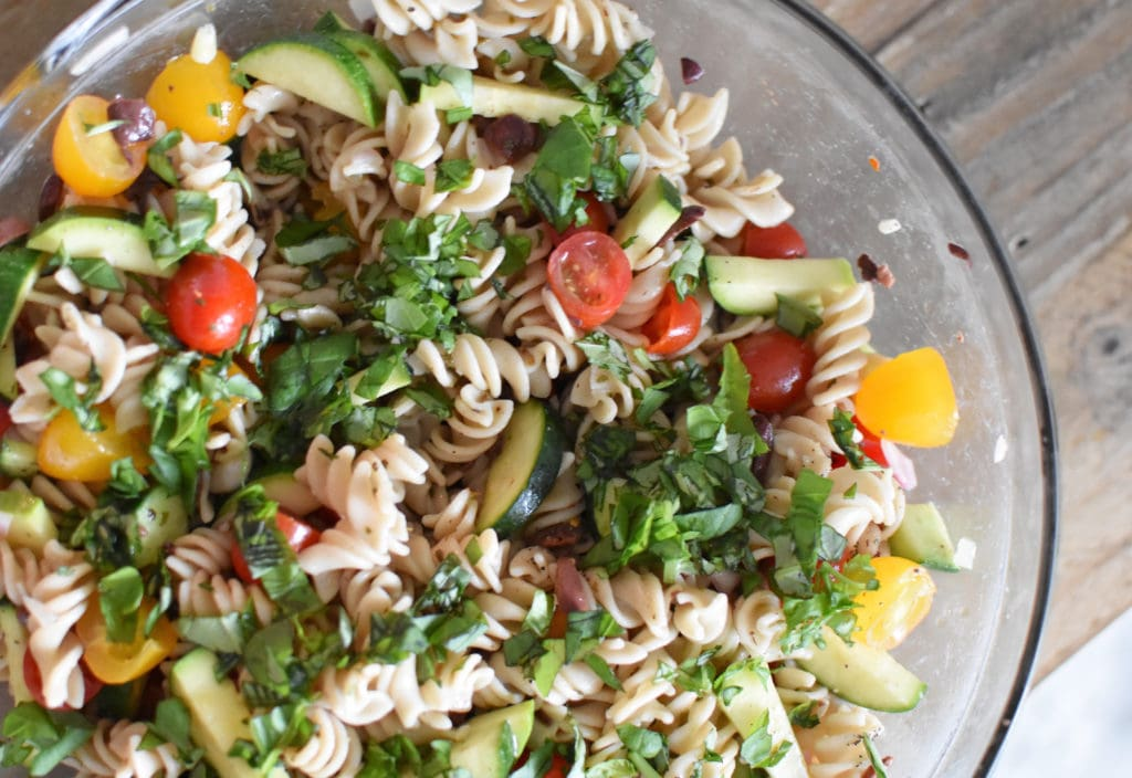 A bowl of gluten free pasta salad with herbs sprinkled on top