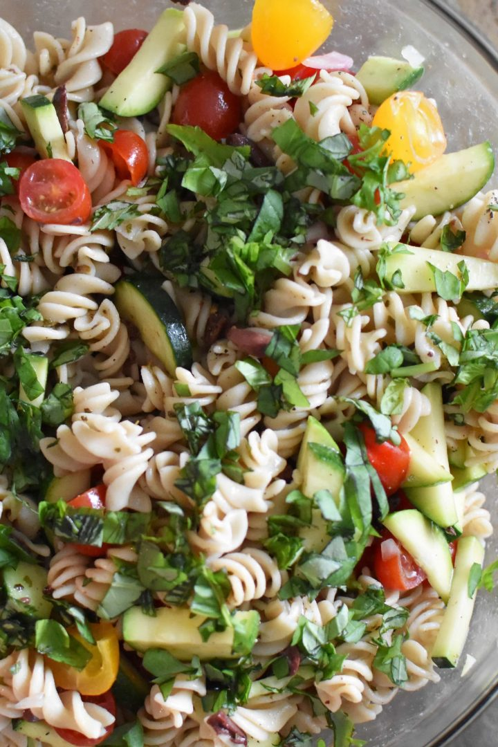 A bowl of gluten free pasta salad mixed with fresh vegetables on a wooden table