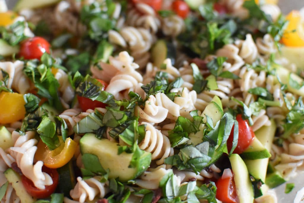 Fusilli pasta mixed with tomatoes and zucchini and topped with lots of herbs