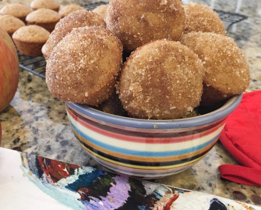 Cinnamon apple cider donut holes in a bowl next to apples