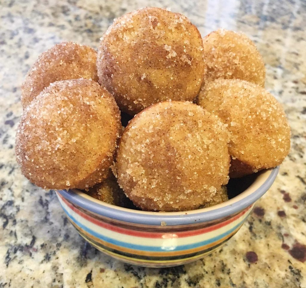Donut holes crusted in cinnamon sugar in a colorful bowl on a table
