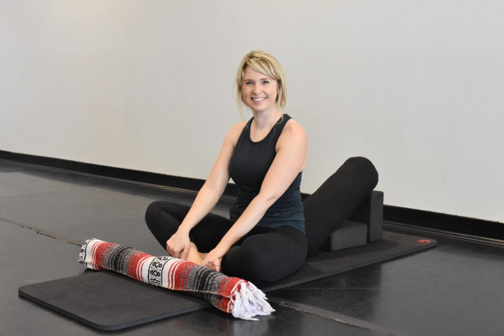 A woman on a yoga mat smiling while setting up a supported savasana during yoga for vestibular disorders
