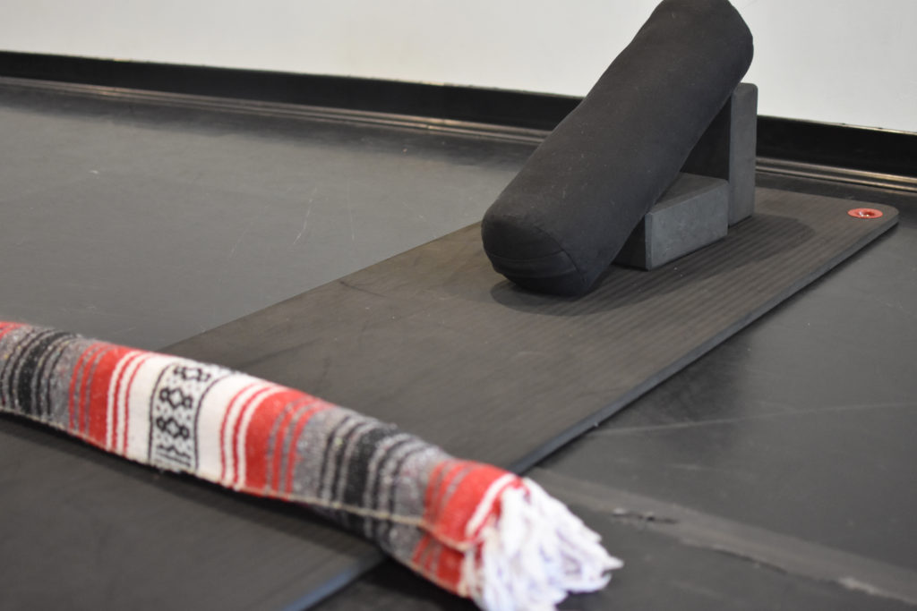 A bolster and block set up on a yoga mat for supported savasana