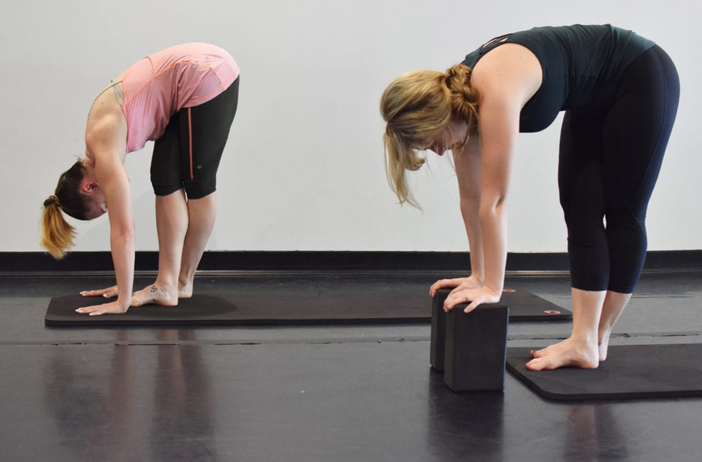 Two women bending over practicing restorative yoga for vestibular disorders