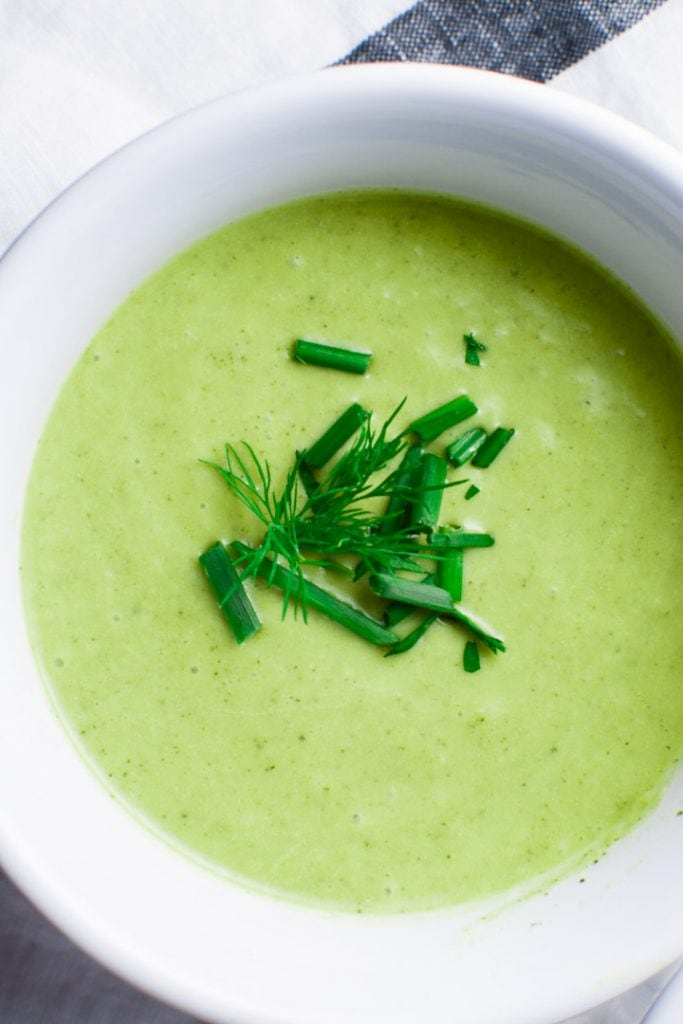 A white bowl filled with creamy cold zucchini soup topped with chives on a napkin