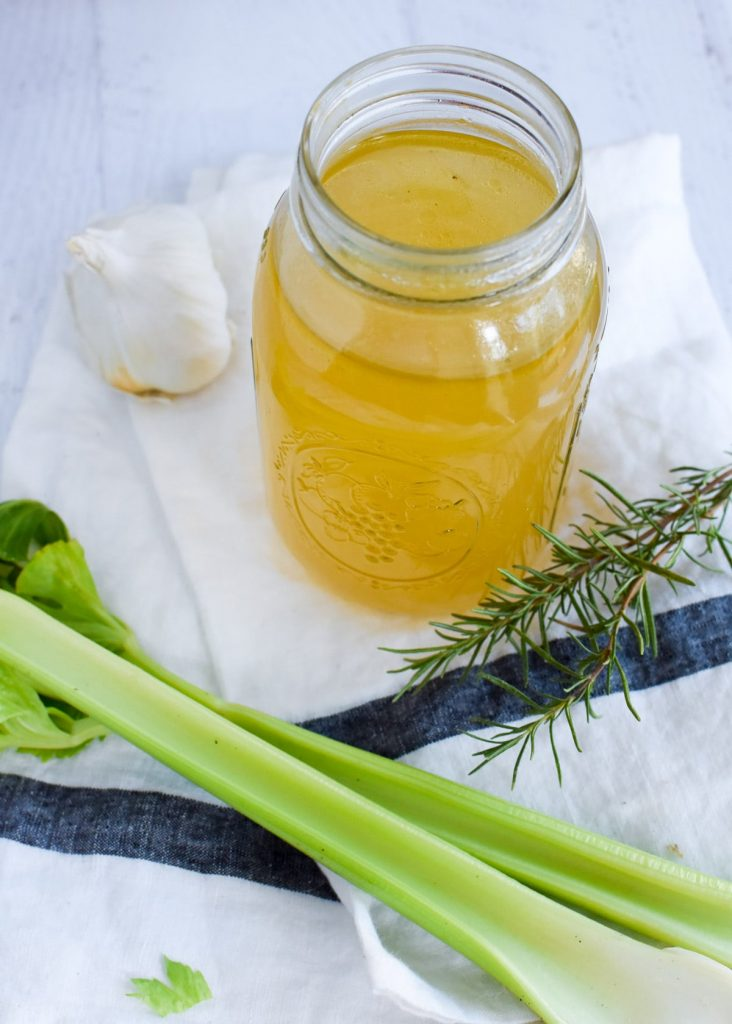 Broth in a clear glass with celery and rosemary on a white towel