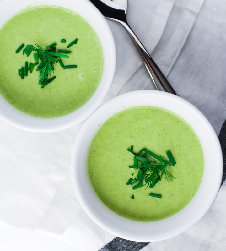 Two bowls of green zucchini soup topped with dill next to spoons