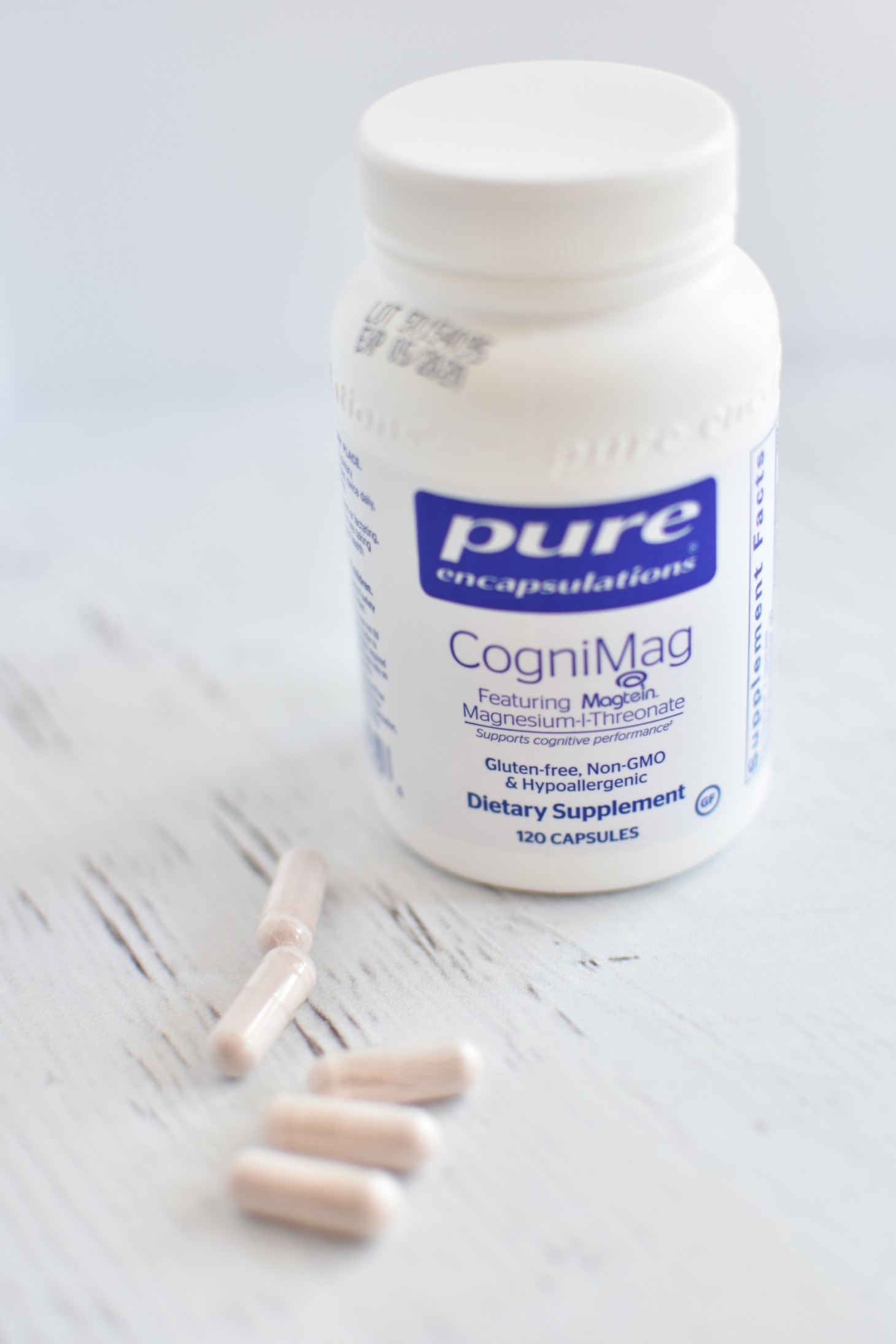 pure encapsulations cognimag bottle with a few pills on a white table