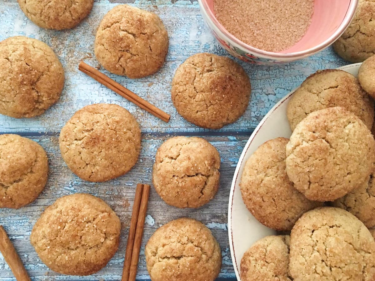Snickerdoodles with cinnamon sticks and a bowl of cinnamon sugar