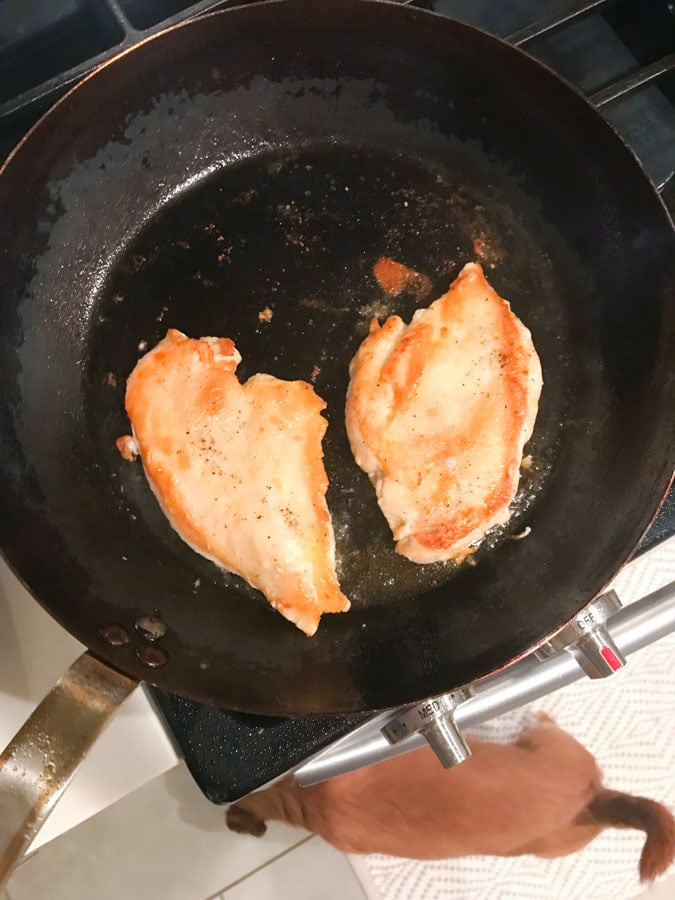 Chicken being seared in pan for chicken marsala