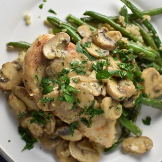 Chicken with mushrooms and green beans on a grey plate with a blue napkin