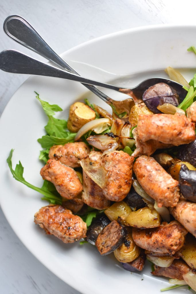 Looking for an easy, one pan dinner? This salad with arugula is topped with sweet roasted shallots, potatoes, and chicken sausage for the perfect, healthy fall meal that's gluten free and whole 30 #healthy #weeknightdinner #migrainediet