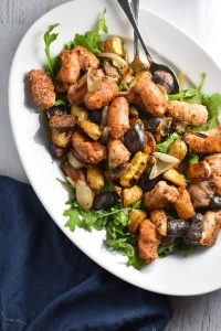 Looking for an easy, one pan dinner? This salad with arugula is topped with sweet roasted shallots, potatoes, and chicken sausage for the perfect, healthy fall meal that's gluten free and whole 30 #healthy #weeknightdinner #migrainediet #whole30