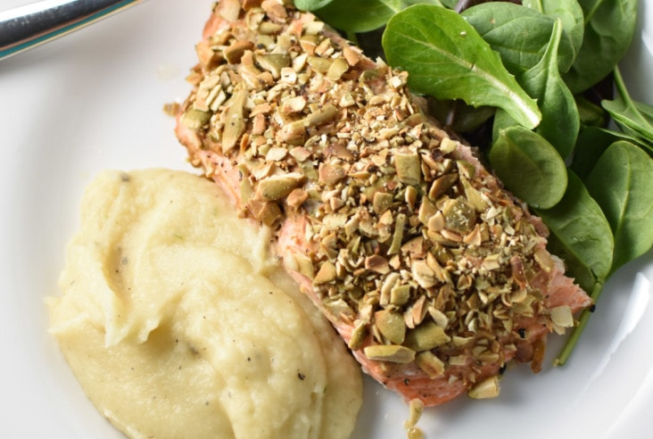 Pepita crusted salmon on a white plate with a fork and mashed potatoes with lettuce