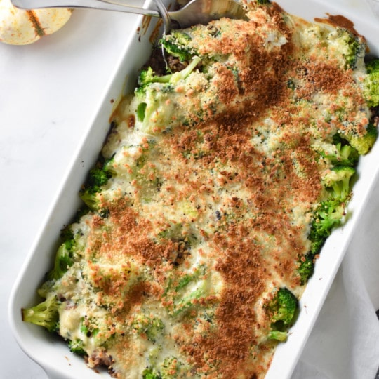 Serving spoons sticking into a broccoli rice casserole on a white surface