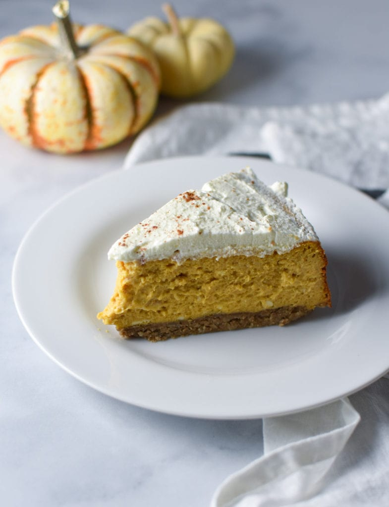 a slice of pumpkin cheesecake on a white plate with two pumpkins in the back