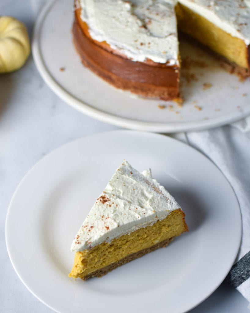 a slice of pumpkin cheesecake on a white plate with a whole cheesecake in the background